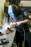 Auto mechanic welding - job site photography.